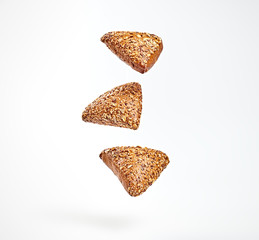 Photo Blinds Bread Multigrain bun flying in air. Fresh baked cookie with sunflower, flax, sesame falling on white. Delicious healthy bread bakery product with different seed. Levitation, fly dieting baking concept