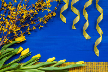 Spring And Easter Decoration. Yellow Tulip Flowers, Branch And Ribbon. Blue Wooden Background