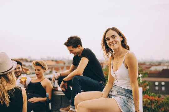 Smiling young woman sitting with friends at rooftop party