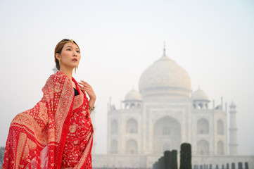 Portrait of young woman in red saree indian traditional dress against Taj Mahal, Agra, India Fototapete