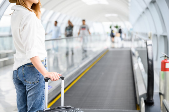 Vacation and summer concept, A woman with suitcase walking in airport terminal