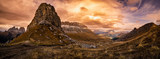 Autumn alpine Dolomites mountain dramatic sunset scene near Pordoi Pass, Trentino, Italy. Picturesque traveling, seasonal, nature and countryside beauty concept scene.