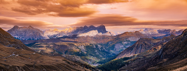 Autumn evening alpine Dolomites mountain dramatic sunset scene near Pordoi Pass, Trentino, Italy. Picturesque traveling, seasonal, nature and countryside beauty concept.