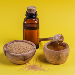 Ingredient for make homemade sugaring wax. Brown sugar, honey and oil on yellow background