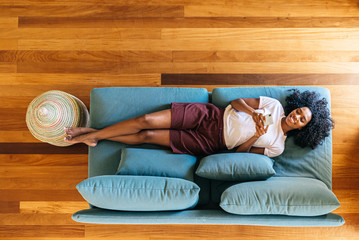 Black woman chatting on smartphone lying on couch at home