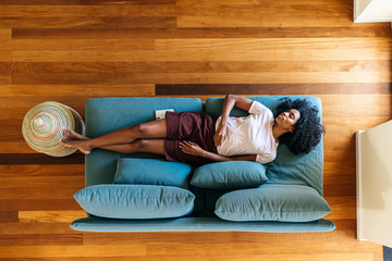 Young black lady sleeping on sofa at home