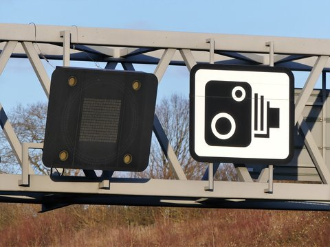 Speed camera sign and variable speed limit display on gantry above the M25 London Orbital Motorway in Hertfordshire, England, UK