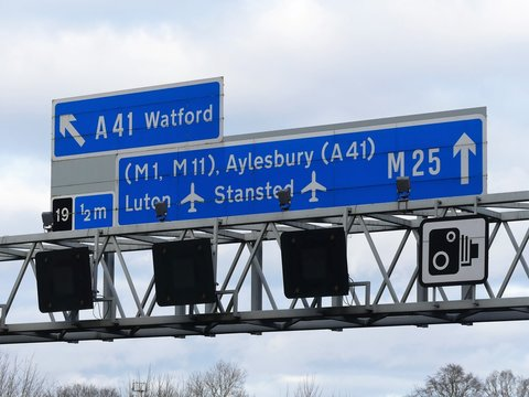 M25 Motorway signs and electronic displays on gantry, near Junction 19 in Hertfordshire, UK