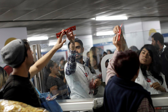 Members of an organization give out free condoms during an event organized by AIDS Healthcare Foundation for the International Condom Day, at a metro station in Mexico City