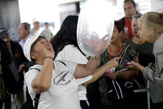 A member of an organization holds an inflated condom during an event organized by AIDS Healthcare Foundation for the International Condom Day, at a metro station in Mexico City