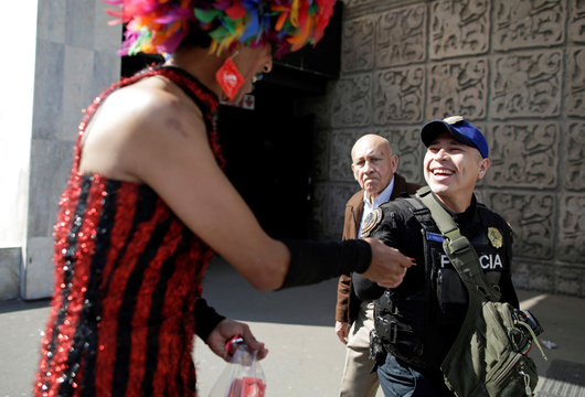 Polo Gomez, also known as drag queen Yolanda la del Rio, from organization Condomovil A.C., gives out a free condom to a police officer during an event organized by AIDS Healthcare Foundation for the International Condom Day, in Mexico City