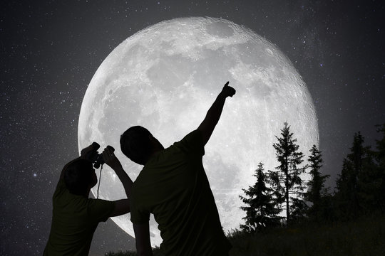 Silhouettes of people observing stars in night sky. Moon in back