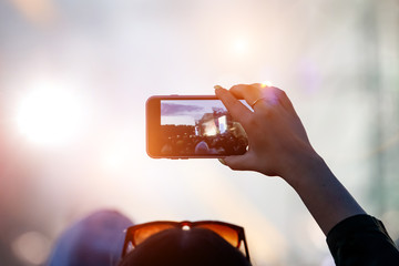Fan at outdoor music festival taking pictures and making videos using his smartphone.