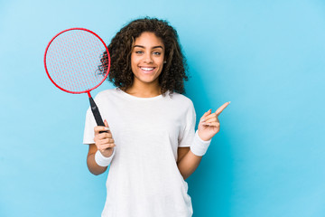 Young african american woman playing badminton smiling and pointing aside, showing something at...