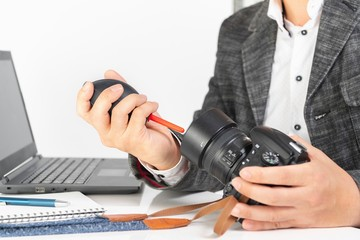 デジタルカメラのレンズを掃除する男性