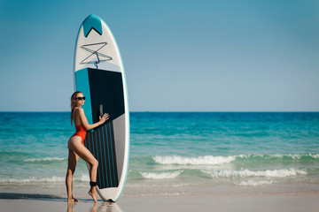 Attractive young woman in swimsuit with Stand Up Paddle Board, for SUP surfing, on the beach near the ocean. Activity sports and active lifestyle concept
