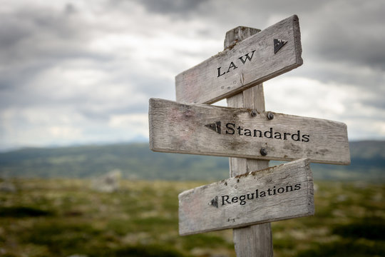 Law, standards and regulations text on wooden road sign outdoors in nature.