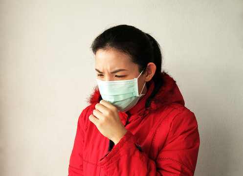 Asian woman wearing face mask and coughing on white wall background. Concept for air pollution, coronavirus infection and health care.