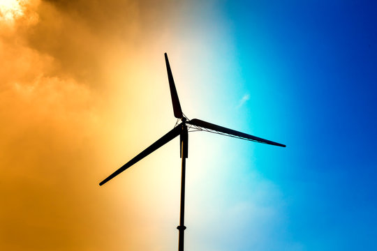 Silhouette wind turbine with half orange sky and half bright sky background, small wind turbine renewable green energy source for future
