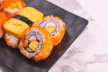 Autocollant pour porte Sushi bar Sushi Roll with salmon, sushi maki roll and tamago sushi on black plate