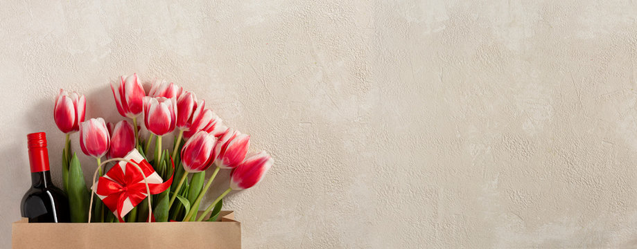 Happy birthday greetings concept. St. Valentine's Day, Mother's Day. Spring fresh flowers, wine, gift