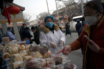 Woman wearing a face mask buys food from a stall set up by a restaurant outside its outlet near Drum Tower in Beiing
