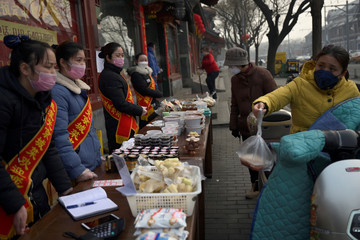 People wearing face masks buy food from a stall set up by a restaurant in Beijing