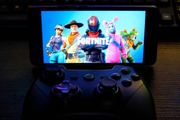 Kostanay, Kazakhstan, February 12, 2020.Joystick and mobile phone with the logo of the popular game fortnite , from Epic Games.