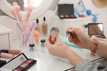 Woman applying makeup at dressing table, closeup