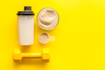 Sport diet. Protein shake near dumbbells on yellow background top-down flat lay copy space