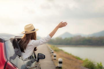 Woman at spree time relaxing and enjoying road trip. Young Asian happines female wearing hat inside compact black car with raise her hand out to the car window with mountain and lake view at sunny day