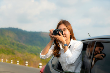 Young Asian Woman tourist taking photo in car with camera driving on road trip travel vacation. Girl passenger taking picture out of window with beautiful view lake and mountains in background..