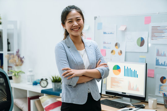 Young asian chinese woman freelancer stay indoors home office concept. confident female worker in smart casual wear with arms crossed face camera smiling with white board and documents on background.