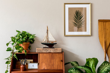 Stylish retro composition of home office interior with vintage wooden cabinet, ship, plants, clock, paddle and elegant accessories. Gold mock up poster frame. Retro home decor. Marine concept Template