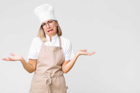 middle age baker woman looking puzzled, confused and stressed, wondering between different options, feeling uncertain against flat wall