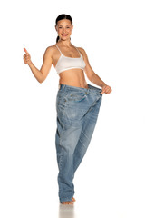 Young slim woman in big size pants showing thumbs up