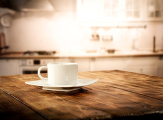 Wall Mural - Table background in kitchen interior and woman hands with cup of coffee