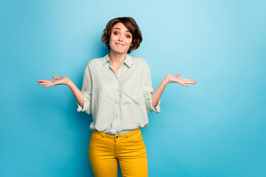 Photo of pretty lady raise hands shrug shoulders do not care friends problems ignoring smile wear casual green shirt yellow trousers isolated blue color background