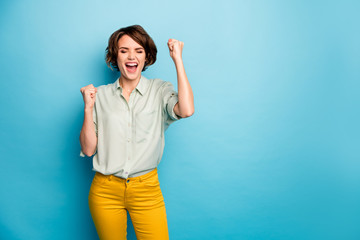 I am rich. Photo of pretty funny lady raise fists screaming loudly celebrating money lottery winning wear casual green shirt yellow trousers isolated blue color background