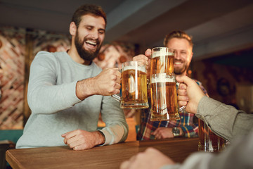 Group of happy friends clinking glasses with beer at a sports bar.