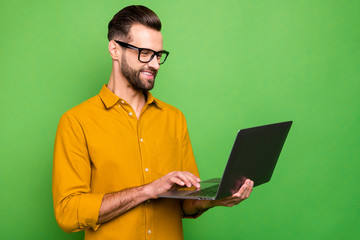 Profile side view portrait of his he nice attractive cheerful cheery intelligent bearded guy in formal shirt working online creating startup isolated on bright vivid shine vibrant green color Wall mural