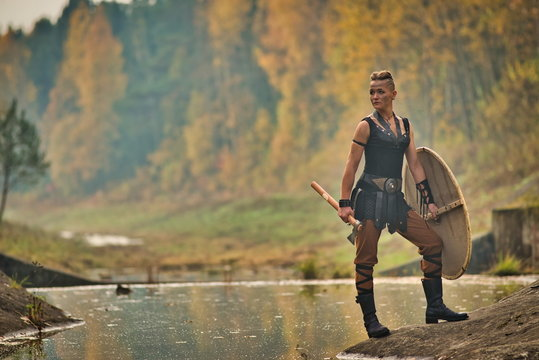 A strong woman, a feminist, a symbol of feminism. Viking woman with axe in a traditional warrior clothes. Against the backdrop of a large viking