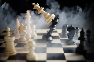 chess queen beats king between other pieces on the chessboard, much smoke over the battle,  against a dark background, concept for aggression, success and competition between teams