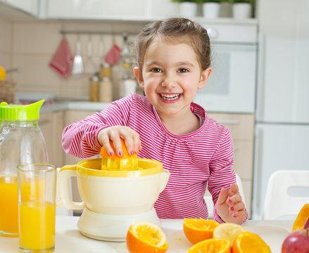 Cheerful little girl making her self an orange juice