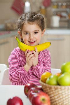 Smiling little girl holding banana