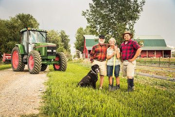 Portrait of farming family laughing after long day of work with dag, tractor and barn. Laurel, Montana, USA