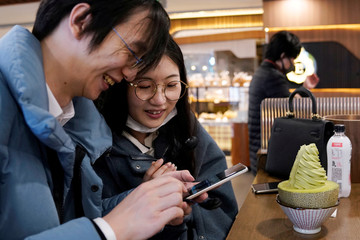 Wang, 32, and his wife Shi, 30, look at their pictures on a phone at a ice cream shop on Valentine's Day in Shanghai