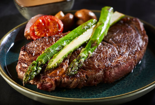 Thick juicy beef steak with green asparagus