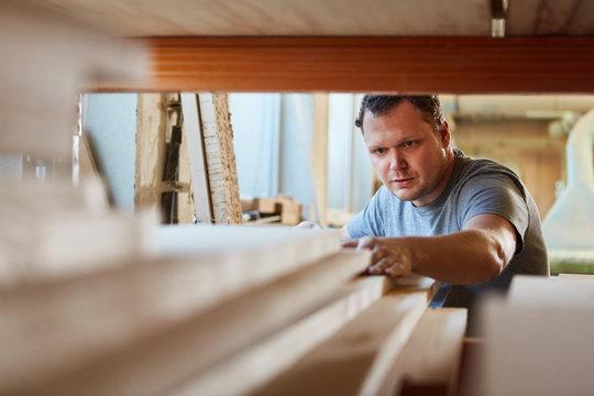Tischler im Lager der Tischlerei sucht nach Holz