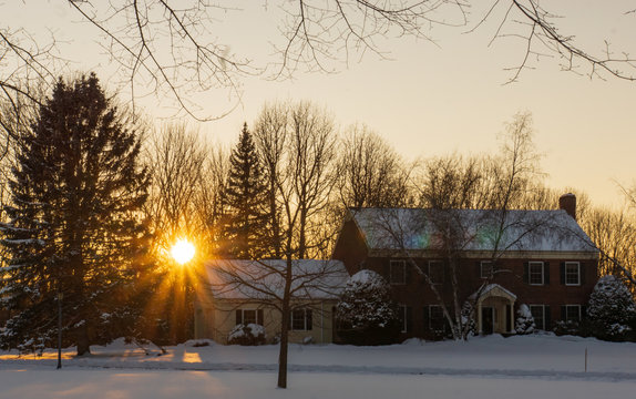 winter scene with sun setting behind home  in New England